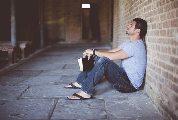 man sits alone against a brick wall