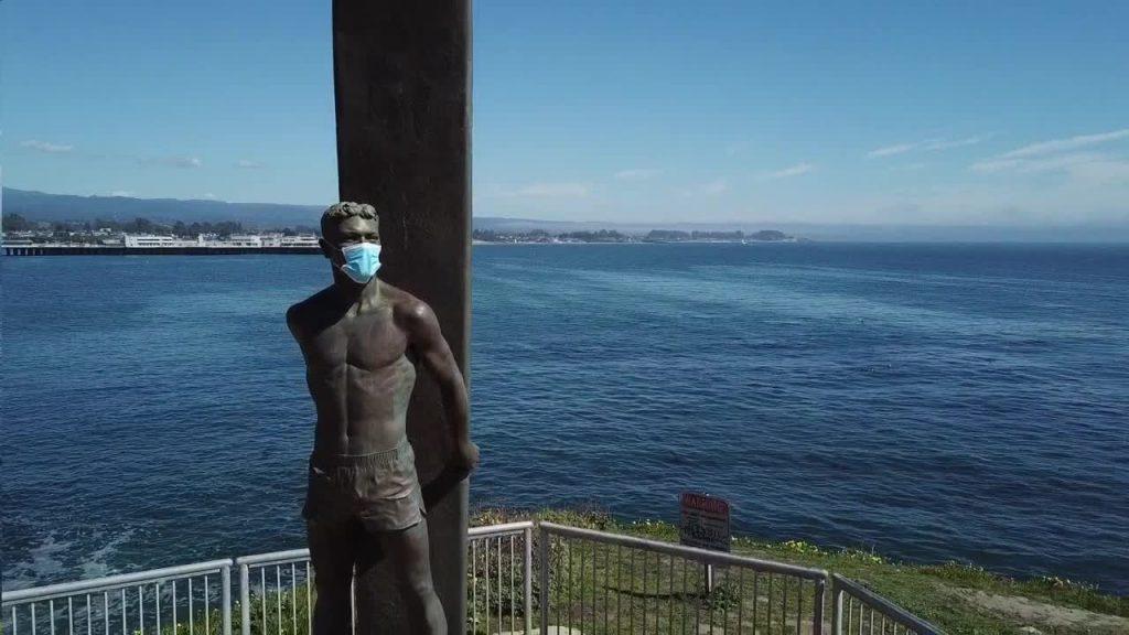 surf statue in santa cruz wears face mask to raise awareness for corona