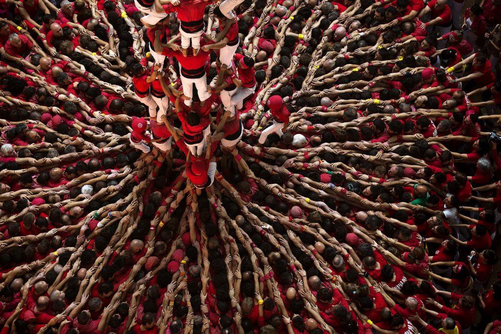 Members of the Castellers Joves Xiquets de Valls try to complete their human tower during the 25th Human Tower Competition in Tarragona, Spain.